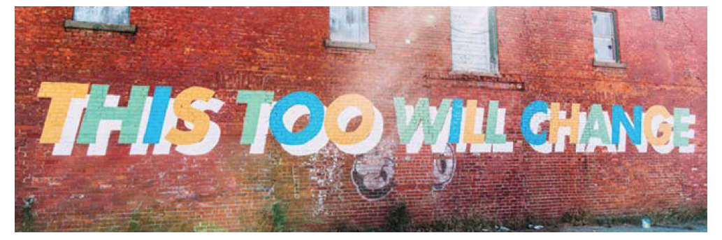 'This too will change' mural on brick wall.